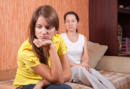 angry teenager: teenager daughter and mother after quarrel at home Stock Photo