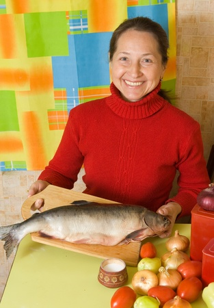 Mature woman with red fish in her kitchen photo