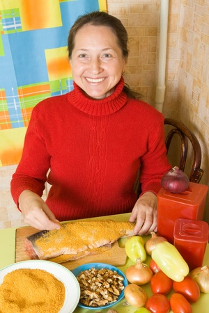 breading: Mature woman is breading salmon  fish  in kitchen