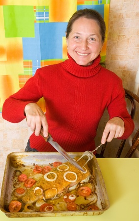 Mature woman slicing breaded fish in cook griddle photo