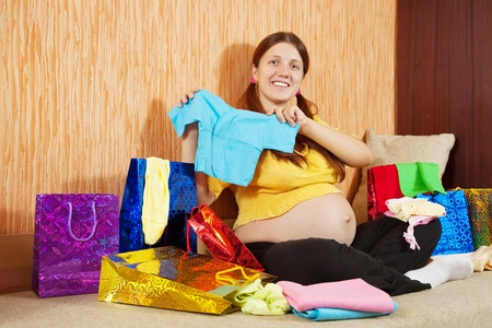 pregnant woman with shopping bags and babies clothes at home photo
