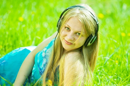 girl listening music and lying on grass photo