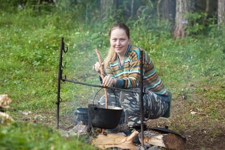 キャンプ オープン火災で大釜で新鮮な食品を調理の女性観光客
