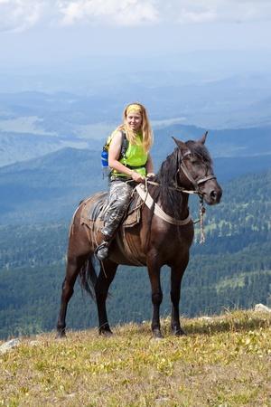 Female rider on horseback at mountains peak photo