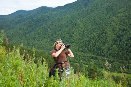 photographer tourist takes pictures nature at mountains Stock Photo - 10769845