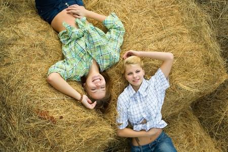 barn girls: Pretty girls in checked shirts resting on hay  Stock Photo