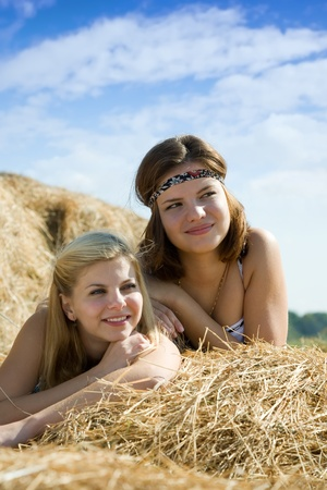 barn girls: country girls laying on hay bail at farm