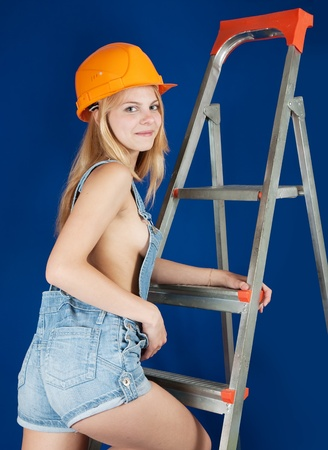 studio happy overall: Sexy girl in dungarees and hardhat on stepladder over blue