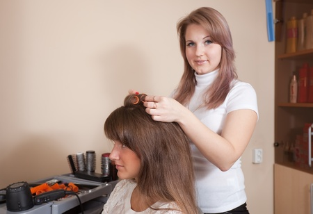 hairtician: Female hairdresser works on woman hair in salon. Focus on customer Stock Photo