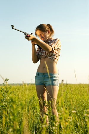 young woman aiming pneumatic air rifle outdoor photo