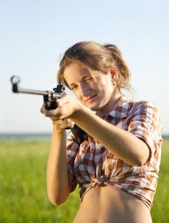 airgun: girl  aiming a pneumatic rifle  against summer field