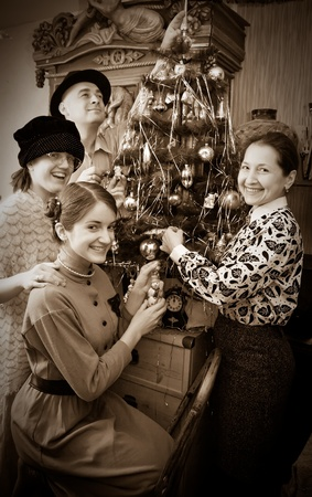decorating christmas tree: Vintage photo of Family decorating Christmas tree at home