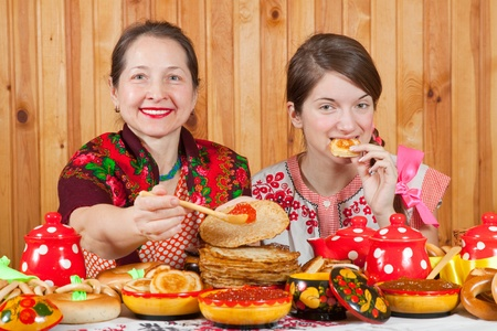 Women in traditional  clothes eating pancake with caviare during  Shrovetide photo