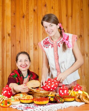 manjar: Mujeres en ropas tradicionales con panqueque durante Carnaval Foto de archivo
