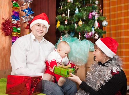 Happy family of three  celebrating Christmas at home photo