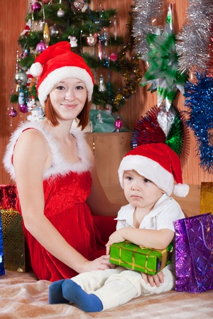 Little boy and mother in Santa hat at home Stock Photo - 10812805