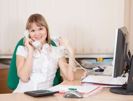 female  manager speaking by two phone in office photo
