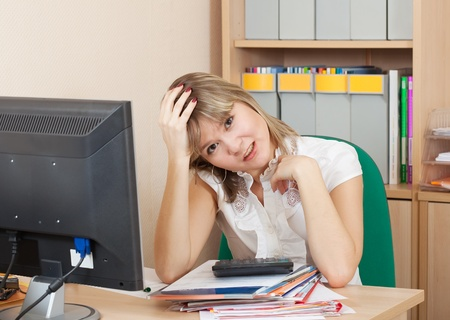 weariness: weariness woman  sitting with documents  on workplace in  office