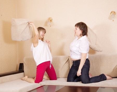 Happy girls fighting with pillows  on sofa in livingroom at home Stock Photo - 10812763