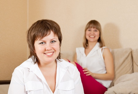 chuckle: Two happy casual girls in home interior