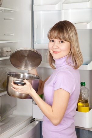 Young woman looking into pan from  refrigerator Stock Photo - 10812794