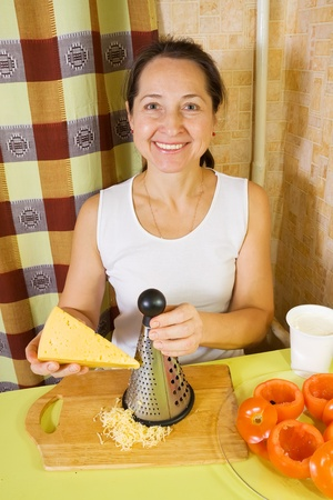 farci: Woman grating cheese. See in series stages of cooking of farci tomato salad Stock Photo