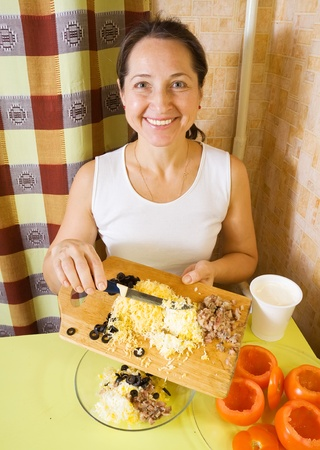 farci: Woman making stuff  for  farci tomato salad. See in series stages of cooking of farci tomato  salad
