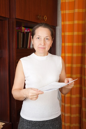 lamentable: Sad mature woman with utility bills  at her home