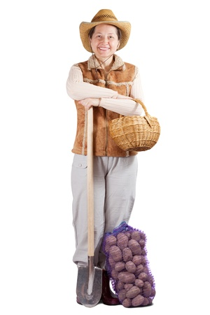 welly: Happy pastoral  woman  with spade and harvested potato over white Stock Photo