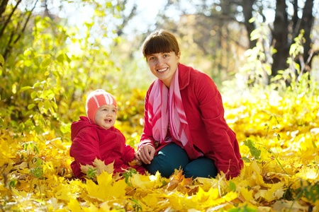 Mother and   baby sitting on maple leaves in autumn park photo