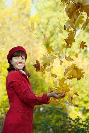 Young woman in red coat throwing yellow maple leaves in autumn Stock Photo - 10885911