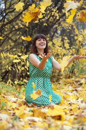happy seasonable: Girl in dress throwing leaves in the air