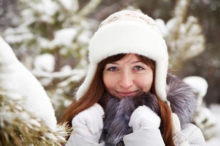 fur tree: smiling woman wearing white cap in wintry park