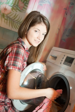 Teenager girl putting clothes in to washing machine and smiling photo