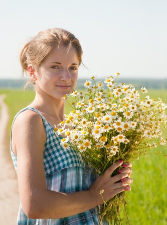 girl with bouquet of camomiles at summer field photo