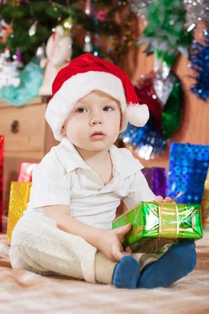 クリスマス ギフトを自宅で座っている小さな男の子