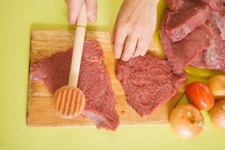 ingridients: Closeup of cook hands making meat tenderizer with meat hammer. One of the stages of preparation of the stuffed beef.  See series Stock Photo