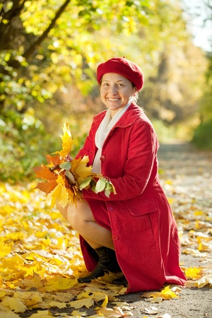 Outdoor portrait of  happy mature woman with maple posy photo