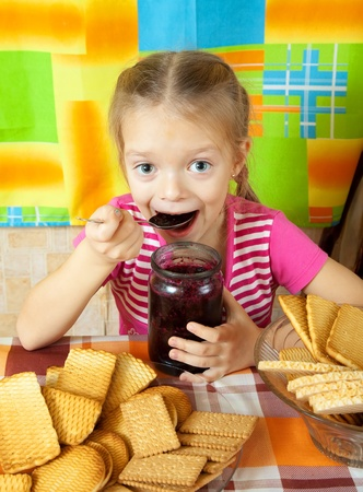 Little girl eating jam from  jar at kitchen Stock Photo - 10998943