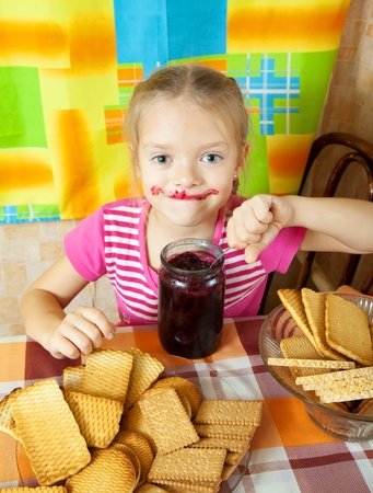 Little girl eating jam from  jar at kitchen Stock Photo - 10998939
