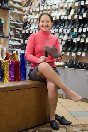Mature woman shopping at fashion shoes shop photo