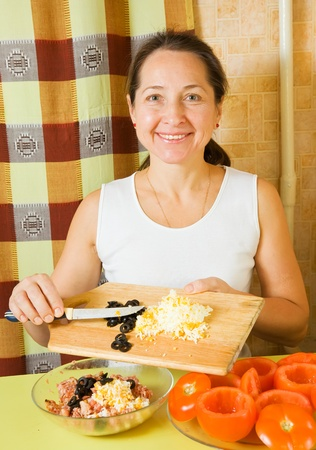 farcie: Mature Woman adds grated eggs and  sliced olives in mincemeat. See in series stages of cooking of stuffed tomato  Stock Photo