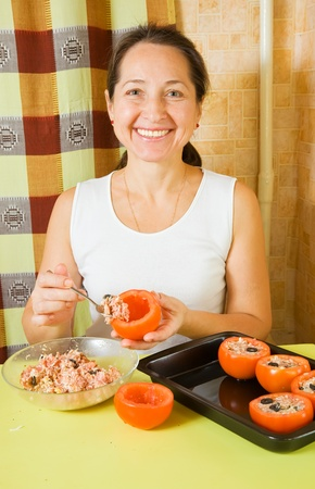 farci: Woman making stuffed tomato in her kitchen. See in series stages of cooking of farci tomato  Stock Photo