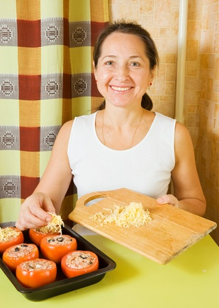 farci: Woman adds cheese to stuffed tomato in her kitchen. See in series stages of cooking of stuffed tomato Stock Photo