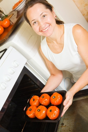 farci: Mature woman roasting stuffed tomato on pan in oven. See in series stages of cooking of farci tomato