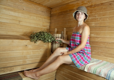 stive: beautiful girl sitting on wooden bench in sauna Stock Photo