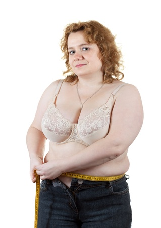 unattractive: Overweight woman measuring waist with tape measure. Isolated over white