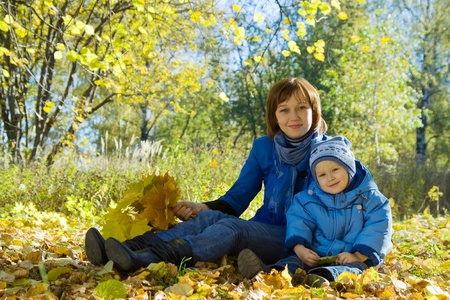 Happy woman with son sitting in autumn park photo