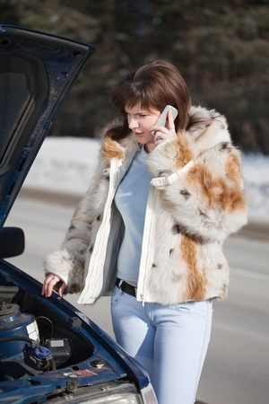 Woman calling by mobile near  her broken car photo