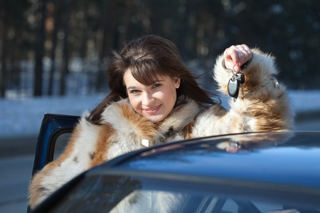 Young woman holding keys to new car photo